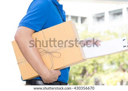 Delivery man holding a parcel box and white paper on clipboard - stock photo