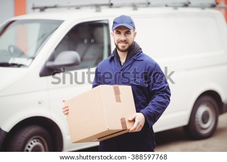 Delivery man holding box in front of his van - stock photo