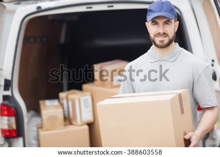 Delivery man holding package in front of his van - stock photo