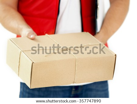 Delivery man in red uniform holding package, close up - stock photo