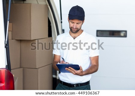 Delivery man is writing on clipboard next to his van in front of a warehouse
