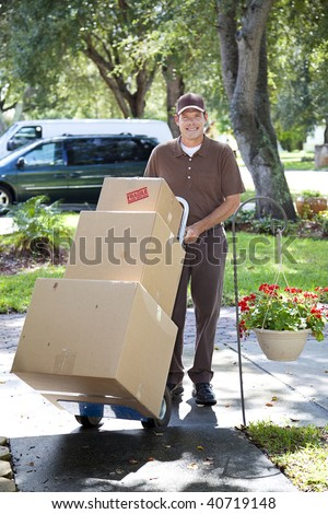 Delivery man or mover bringing boxes up your front walk. - stock photo