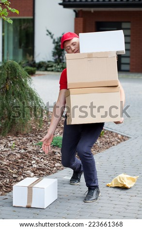 Delivery man picking up packages from the ground - stock photo