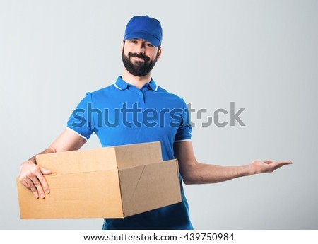 Delivery man presenting something over grey background - stock photo
