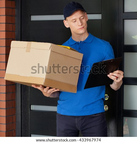 Delivery man with parcel and clipboard waiting at front door - stock photo