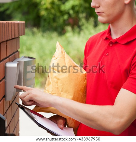 Delivery man with parcel calling client on entryphone - stock photo