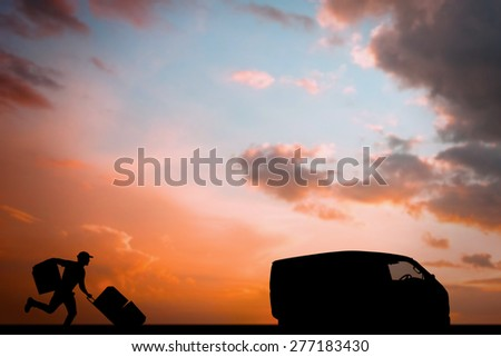 Delivery man with trolley of boxes running against orange and blue sky with clouds - stock photo