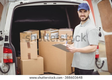 Delivery man writing on clipboard in front of his van - stock photo