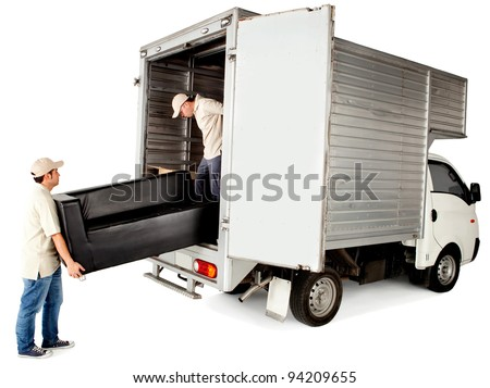 Delivery men loading a sofa in a truck - isolated over white - stock photo