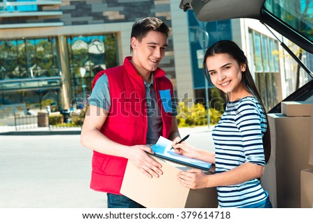Delivery service worker in uniform delivering parcel to woman and standing near car. Man holding box. Woman signing document, smiling and looking at camera - stock photo