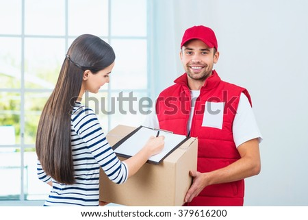 Delivery service worker in uniform delivering parcel to woman. Woman signing document and man smiling and looking at camera - stock photo
