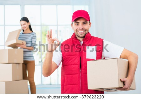 Delivery service worker in uniform delivering parcels to woman. Man with box showing ok sign and looking at camera - stock photo