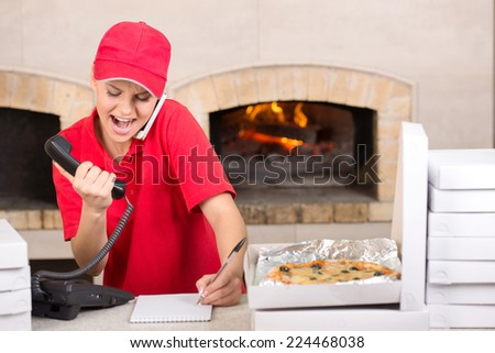 Delivery woman of pizza is taking orders by phone. Several boxes of pizza near her. - stock photo