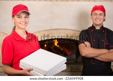 Delivery woman with boxes of pizza in red uniform and chef in black. - stock photo