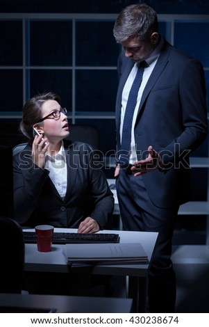 Demanding boss and overworked office worker working at night at office - stock photo