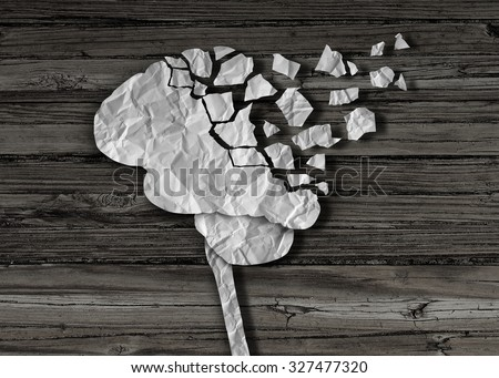 Dementia or brain damage and injury as a mental health and neurology medical symbol with a thinking human organ made of crumpled paper torn in pieces as a creative concept for alzheimer disease. - stock photo