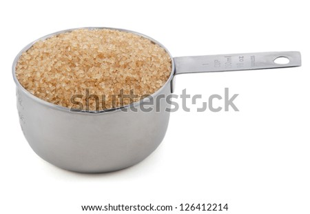 Demerara sugar presented in an American metal cup measure, isolated on a white background - stock photo