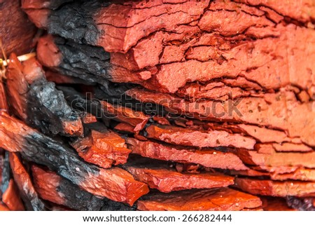 Demolished  brick layering abstraction macro red with black stripe - stock photo