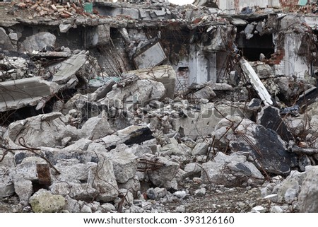 Demolished building with wire reinforced concrete in focus - stock photo