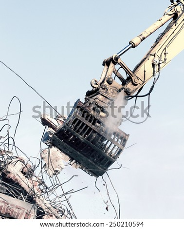Demolition crane dismantling a building - stock photo