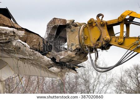Demolition crane dismantling a building - stock photo