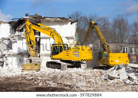 Demolition cranes dismantling a building - stock photo