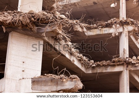 Demolition in progress of obsolete concrete building with lots of steel rebar sticking out of broken down structures - stock photo