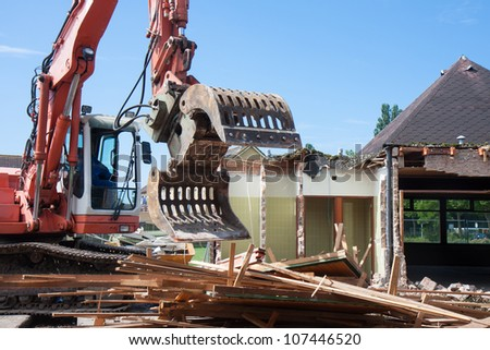 Demolition of a building with a excavator - stock photo