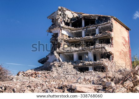 Demolition of buildings in urban environments with heavy machinery