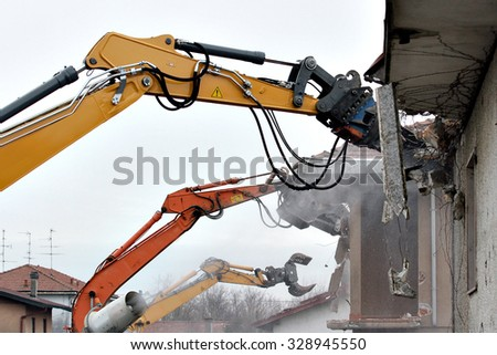 Demolition of houses by hydraulic crashers - stock photo