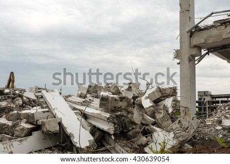 Demolition of large industrial buildings with piles of concrete parts - stock photo
