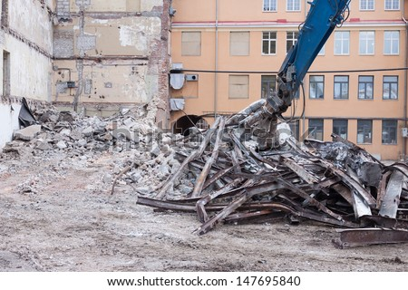 Demolition truck in action. Heap of rubble and a demolished building in the background