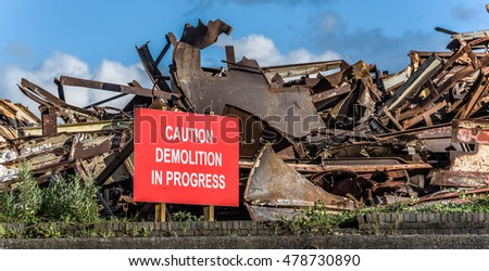 Demolition warning sign with scrap metal structure.