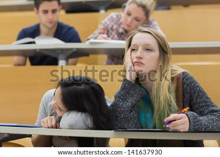 Demotivated students sitting in a lecture hall with one girl napping in college - stock photo