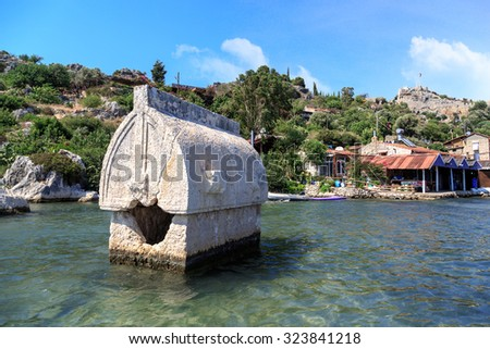 DEMRE, ANTALYA - JULY 18, 2015 : Seascape of Kekova Ancient Lycian City in Antalya, with a big sarcophagus in the sea, on bright blue sky background. - stock photo