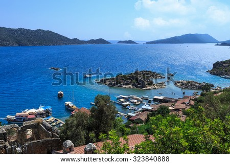 DEMRE, ANTALYA - JULY 18, 2015 : Seascape of Kekova Ancient Lycian City in Antalya, with sailing boats and yachts around, on bright blue sky background. - stock photo