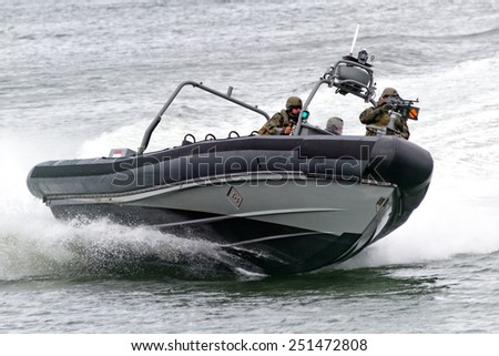 DEN HELDER, THE NETHERLANDS - JUNE 23: Dutch Marines in a speedboat during an assault demo at the Dutch Navy Days on June 23, 2013 in Den Helder, The Netherlands  - stock photo