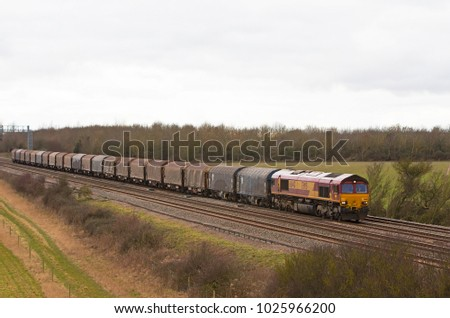 DENCHWORTH, UK - FEBRUARY 19: A DBS operated class 66 diesel loco hauls a rake of empty steel wagons back to the steel works located in south Wales on February 19, 2014 in Denchworth