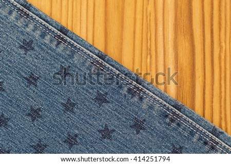 Denim blue jeans with star stamp and white thread seams on wooden background, close up, top view - stock photo