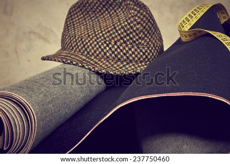 Denim fabric, yellow meter and vintage hat against grunge background - stock photo