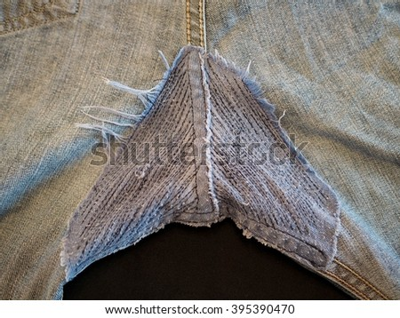 Denim jeans repair. Detail of a patch in blue jeans.Jeans texture. - stock photo