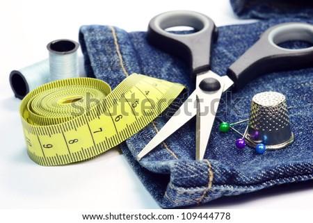 Denim jeans with dressmaking sewing utensils needlework concept - stock photo