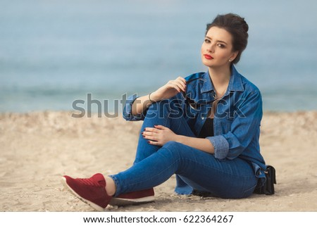 Denim outfit fashion details. Relaxing stylish woman enjoying the sun with red glitter manicure in navy jeans holding sunglasses and leather small cross body bag sitting on the beach.