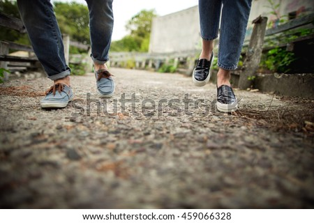 Denim shoes. Girl and boy in denim shoes running outdoors. Selective focus
