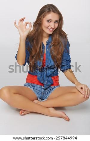 Denim style portrait of teen girl on the floor okay gesturing, over gray background - stock photo