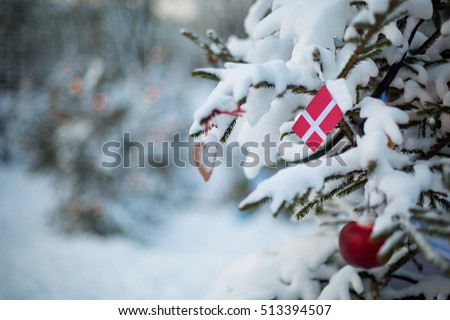 Denmark flag. Christmas holiday greeting card. Christmas tree covered with snow. Scandinavian Winter scene background outdoor