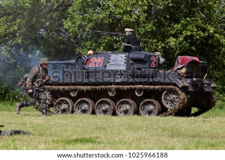 DENMEAD, UK - MAY 25: A replica of a WW2 German Panzer III tank supports an infantry advance on allied lines  during a battle reenactment at the Overlord show on May 25, 2014 in Denmead