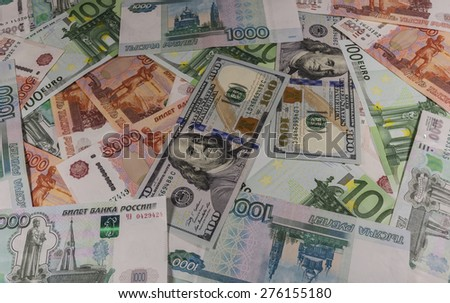 Denominations of 1,000, 5,000 rubles, 100 euros and 100 dollars laid out on the table. - stock photo