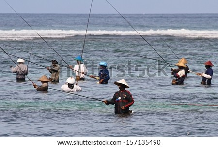 DENPASAR, INDONESIA - APRIL 28: Traditional Balinese fishermen in shallow water on the foreshore of Nusa Dua Beach, Denpasar, Indonesia on April 28, 2013.