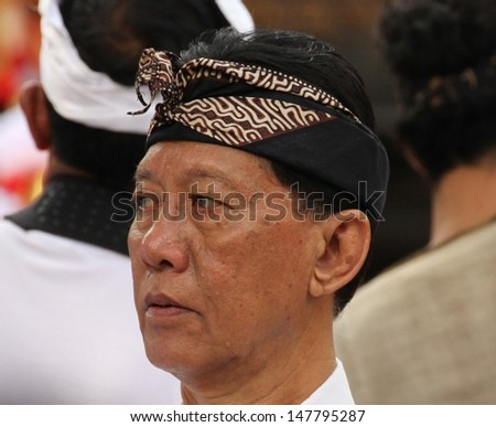 DENPASAR, INDONESIA - MAY 13:  A Balinese man at a Royal Ngaben or cremation ceremony wearing traditional head dress in Ubud, Denpasar, Bali, Indonesia on May 13, 2013.